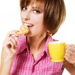 Cute girl with a tea cup biting a pretzel — Stock Photo