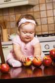 Cute infant girl playing at kitchen — Stock Photo