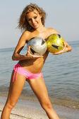 Sexy vrouw met twee voetballen op het strand — Stockfoto