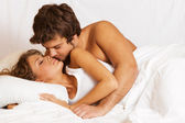 Young beautiful couple in bed — Stock Photo