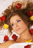 Beautiful young woman lying in rose petals — Stock Photo