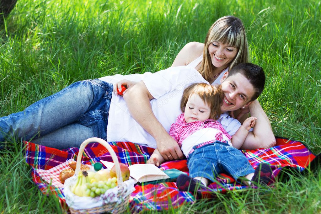 Young beautiful family of three on a picnic  Stock Photo #5757911