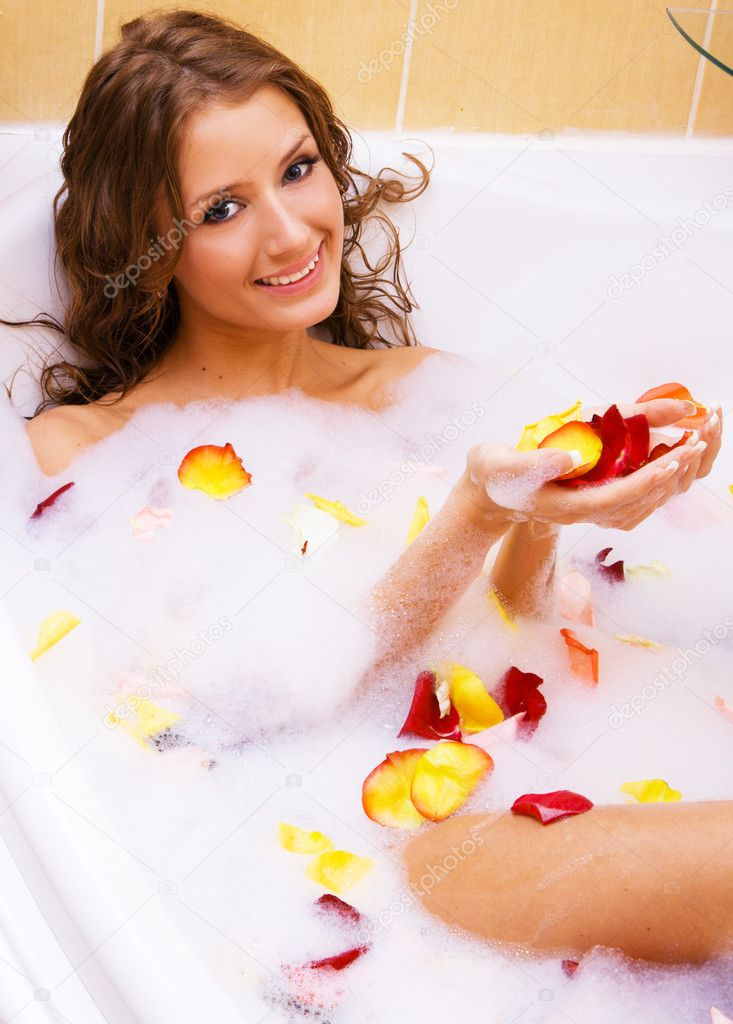 Beautiful lady taking a bath with rose petals — Stock Photo #5758511