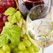 Red and white wine, with bunches of grapes - Stock Photo