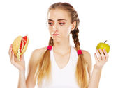 Young woman choosing between hamburger and apple — Stock Photo