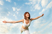 Athletic woman balancing in front of blue sky — Stock Photo