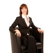 Young business woman sitting in black armchairs — Stock Photo