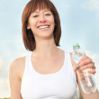 Young athletic woman with bottle of mineral water — Stock Photo #5773492