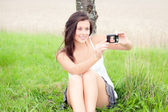 Cute teen taking self-portrait with digital camera — Stock Photo