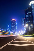 Light trails on the ramp with building background — Stock fotografie