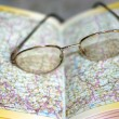 Spectacles on page geographical atlas — Stock Photo