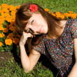 Beautiful girl sitting on meadow with flowers - Stock Photo