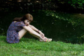 Beautiful girl sitting on bank of a river — Stock Photo
