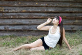 Beautiful girl sitting on hay — Stock Photo