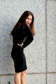 Sexy girl in black dress walking in city — Stock Photo