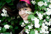 Closeup portrait of a beautiful girl standing among flowers — ストック写真