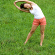 Girl doing exercises in park - Foto Stock