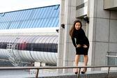 Sexy meisje in zwarte jurk lopen in de stad — Stockfoto