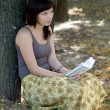 Girl reading book in park - Lizenzfreies Foto