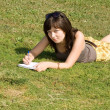 Girl lying on grass in park — Stock fotografie