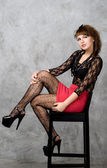 Cute gothic girl sitting on chair studio shot — Stock Photo