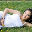 Beautiful pregnant girl lying on grass - Stockfoto