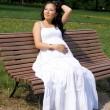 Beautiful pregnant girl walking in park - Stock Photo
