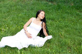 Beautiful pregnant girl sitting on grass — Stock Photo
