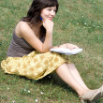 niña sentada en el césped en el parque — Foto de Stock