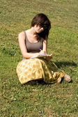 Girl sitting on grass in park — Stock Photo