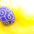 Purple easter egg on yellow feathers — Stock Photo