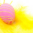 Royalty-Free Stock Photo: Pink easter egg on yellow feathers