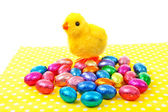 Toy chicken and colorful easter eggs on napkin — Stock Photo