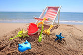 Beach chair near the ocean with toys — Stock Photo