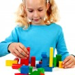 Young blonde girl is playing with colorful wooden blocks — Stock Photo