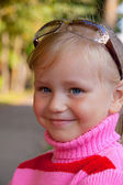 Little blond girl smiling portrait close up in rose sweater — Stock Photo