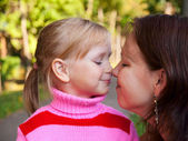 Little blond girl smiling portrait with her mother in a profile — Stock Photo