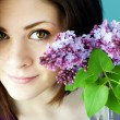 Portrait of young woman with lilacs — Stock Photo