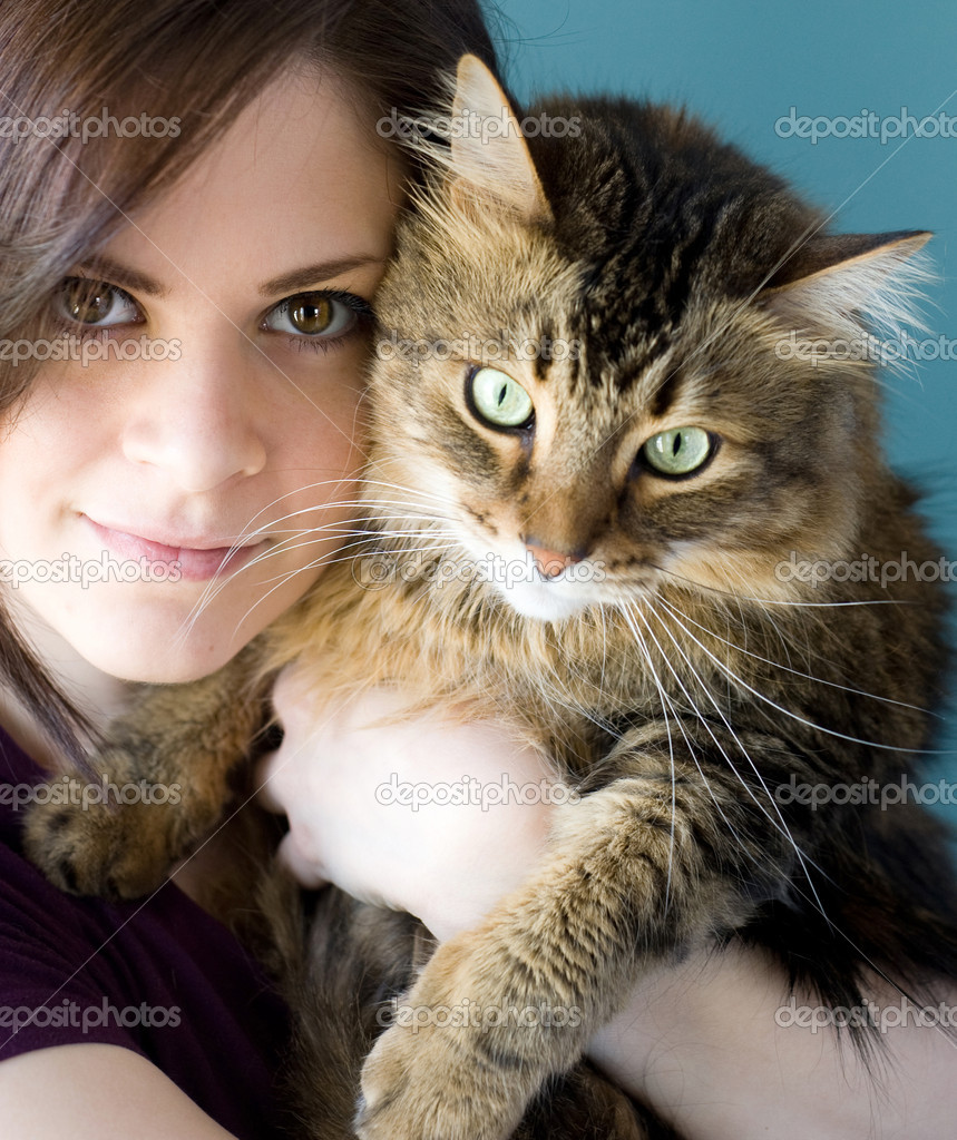 A young woman holding her pet Maine Coon cat.  Stock Photo #5981570