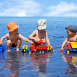 Three boys playing on the beach in the water — Stock Photo