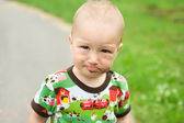 Child with dirty funny face outdoor at playground. — Stock Photo