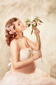 Pregnant woman sniffing flowers and dreaming. — Stock Photo