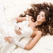Bride with curly long hair lying over white. High angle view. Fa — Stock Photo #6349560