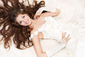 Smiling bride with curly long hair lying over white. High angle — Stock Photo