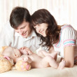 Stock Photo: Young smiling parents looking at baby, play with child. Indoor.