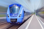 Blue train in motion — Stock Photo