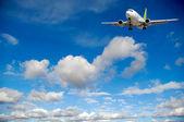 Transporte aéreo - avião voando no céu azul com nuvens — Foto Stock