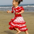 Happy child running on beach - Stock Photo