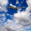 Stock Photo: Air travel - Plane is flying in blue sky with clouds