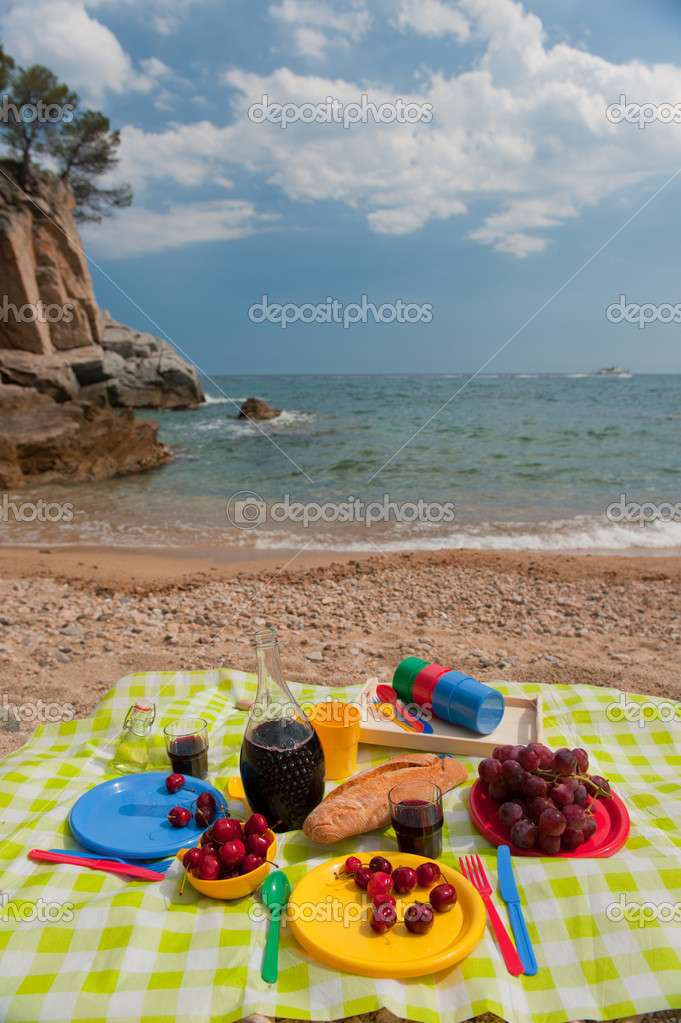 Tasty food on colorful plastic crockery at the beach — Stock Photo #5676751